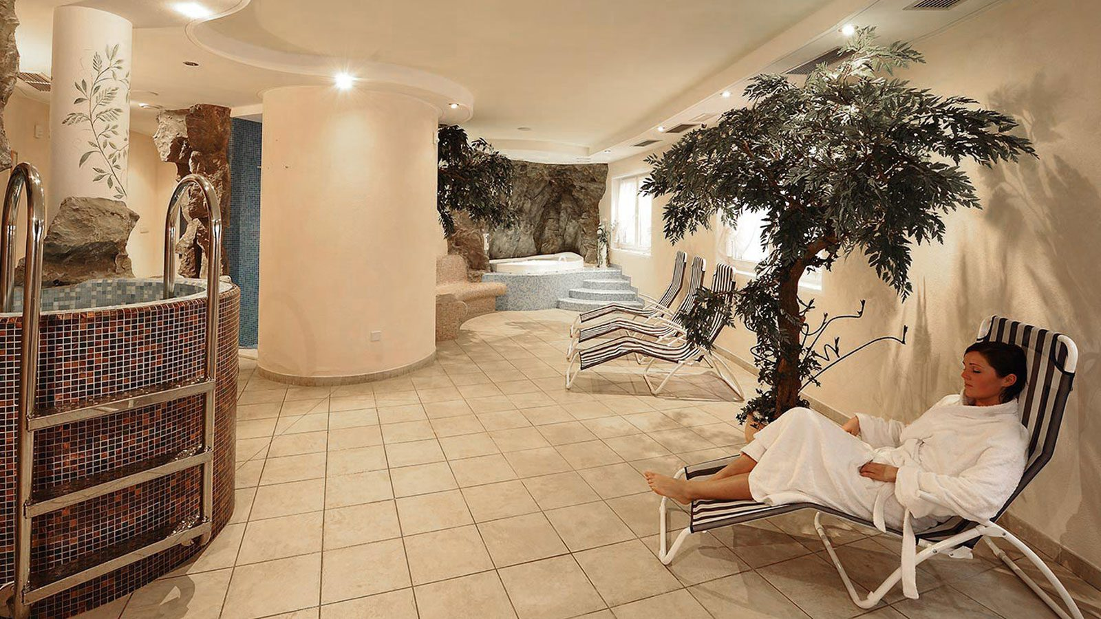 a lady resting on a lounger in the relaxation zone of the wellness area of the Hotel Tyrol in Gsies